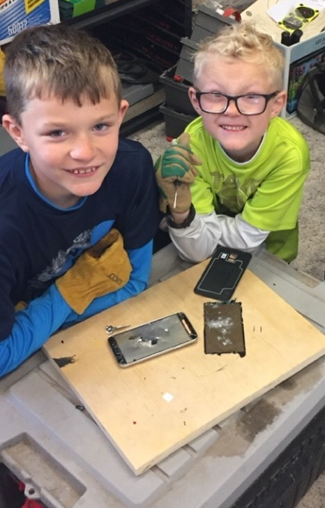 Garrett and Wyatt taking apart a phone and seeing what is inside